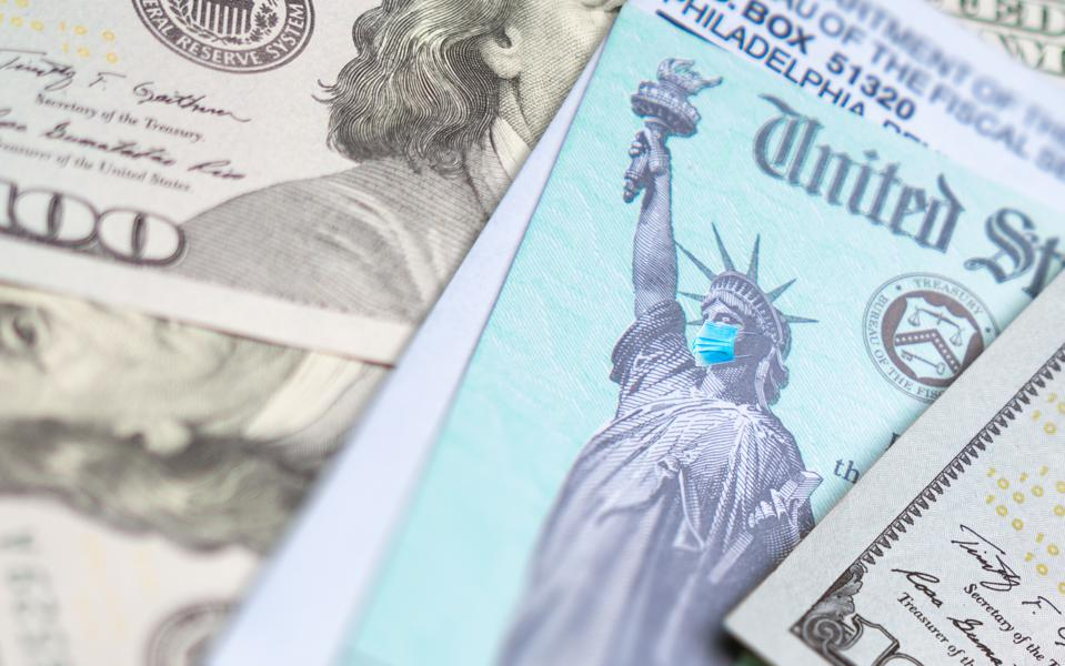 United States IRS Stimulus Check with Statue of Liberty Wearing Medical Face Mask Resting on Money